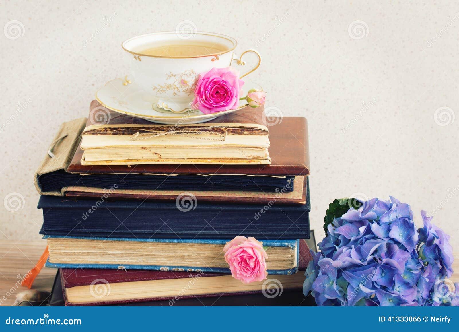 Stapel van oude boeken en post met kop thee