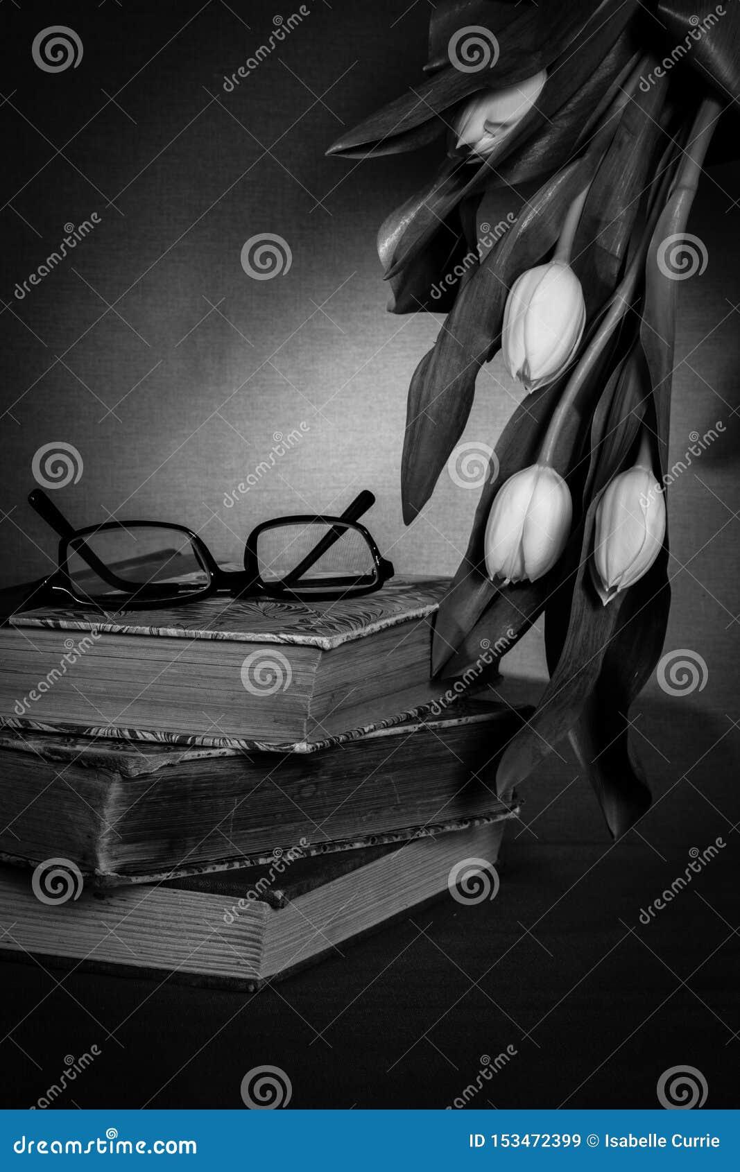 Stapel van oude boeken met paar glazen en witte tulpen