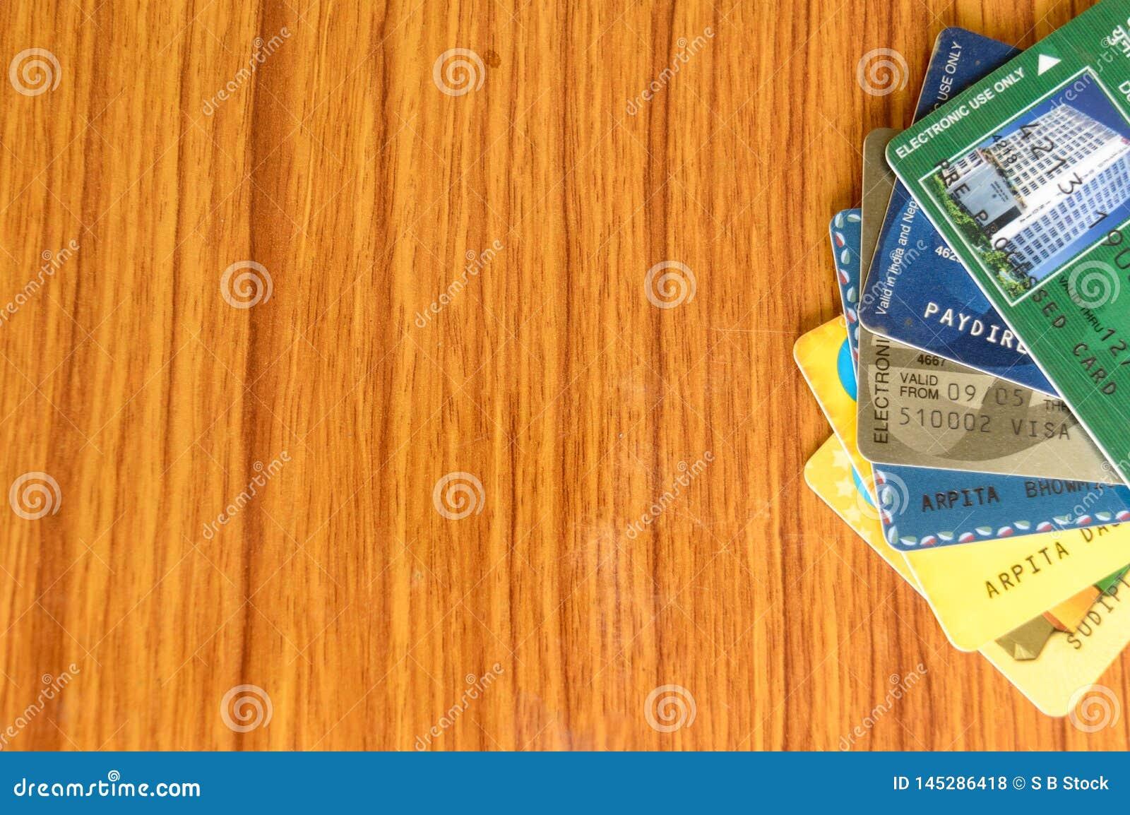 Stapel van verschillende die bankcreditcard bij de rand van houten lijst wordt geplaatst Het product van de bedrijfsfinanci?necon