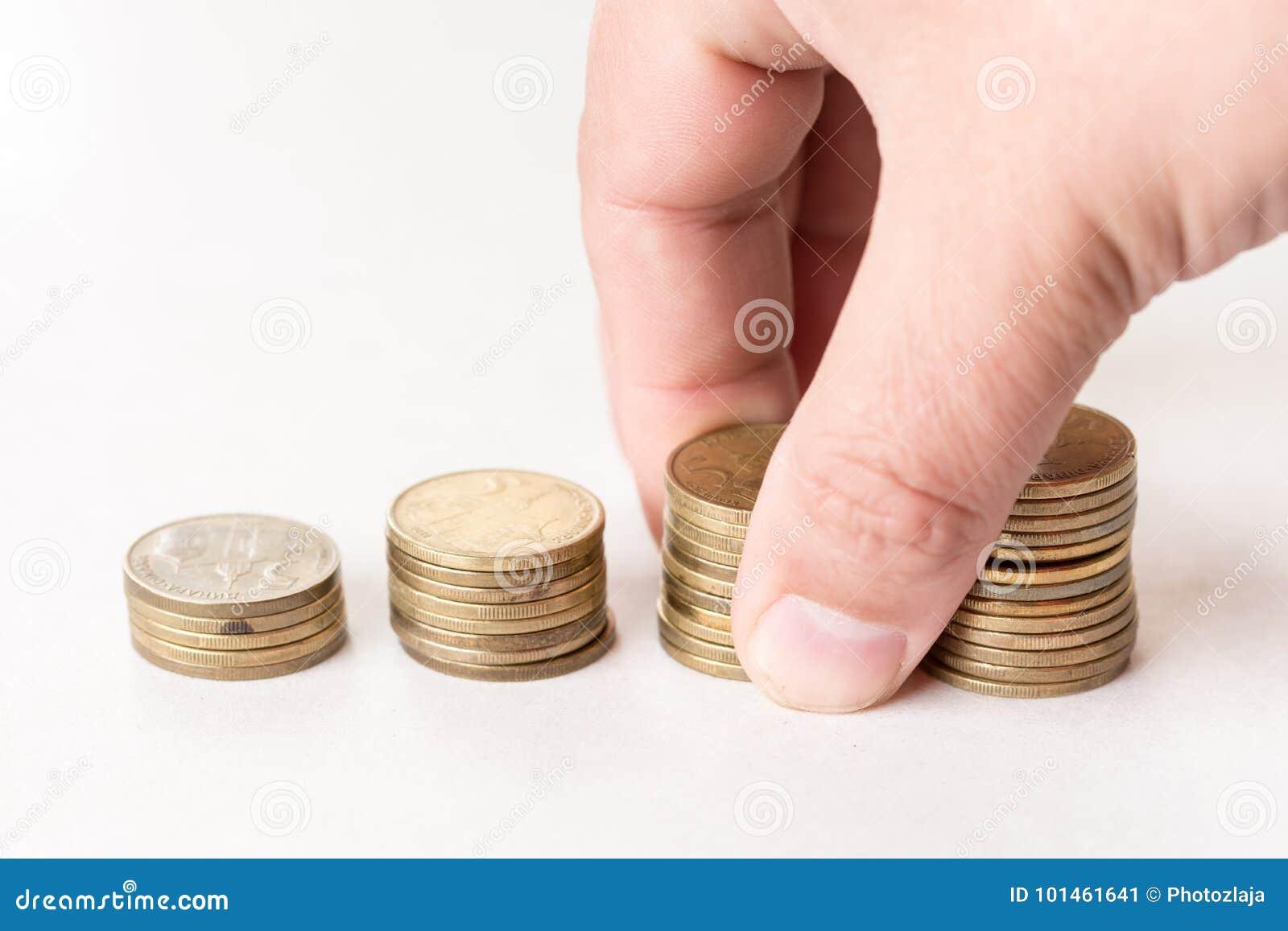 Stapels van metaalmuntstukken boven witte achtergrond en handholdingsstapel van muntstukken