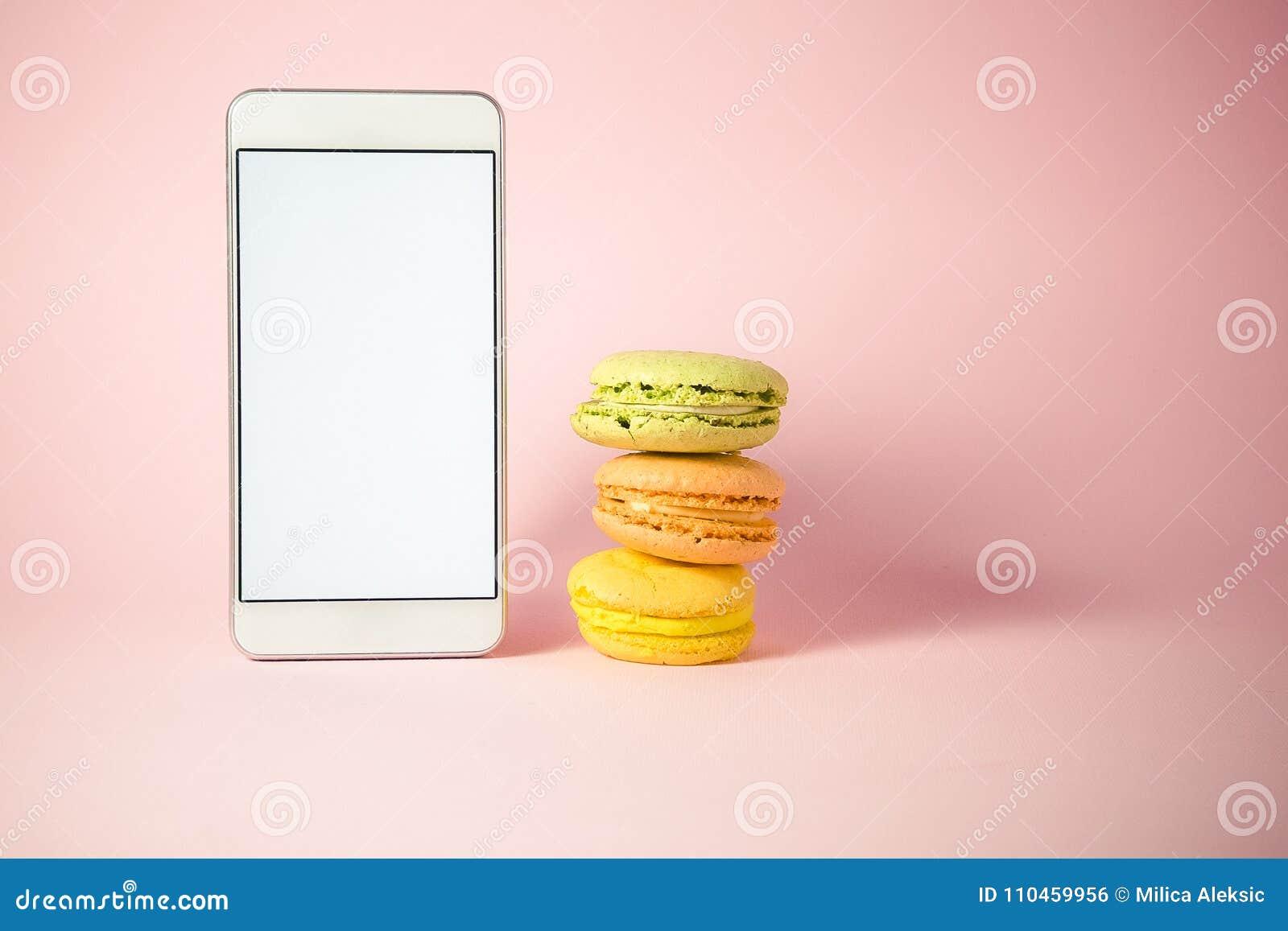 Staplad färgrik macarons och smartphone med den tomma skärmen