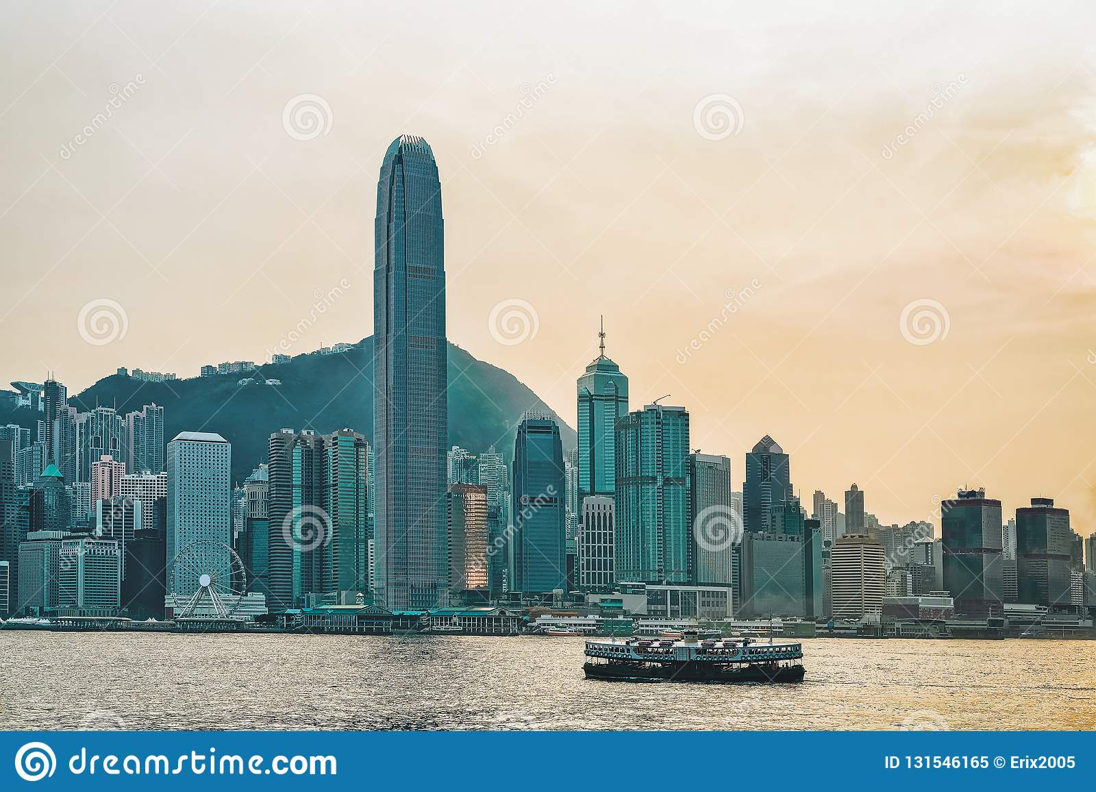 Star ferry in Victoria Harbor and HK skyline at sunset. View from Kowloon on Hong Kong Island royalty free stock photo
