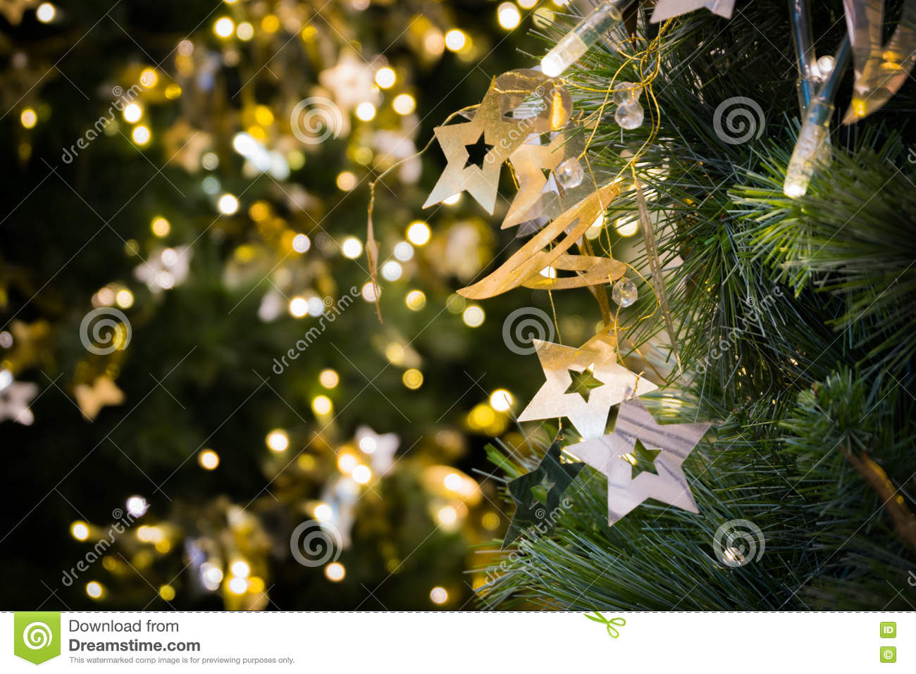 Star hanging on christmas tree with bokeh light in green yellow golden color, holiday abstract background, blur defocused