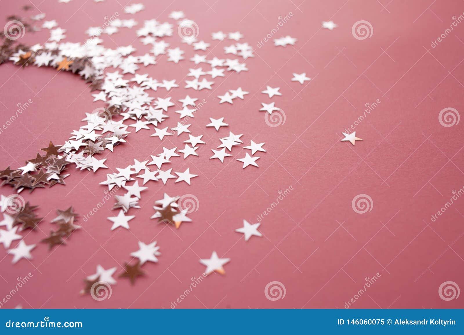 Star-shaped confettien die op een roze achtergrond worden verspreid Viering en partij, concept De ruimte van het exemplaar