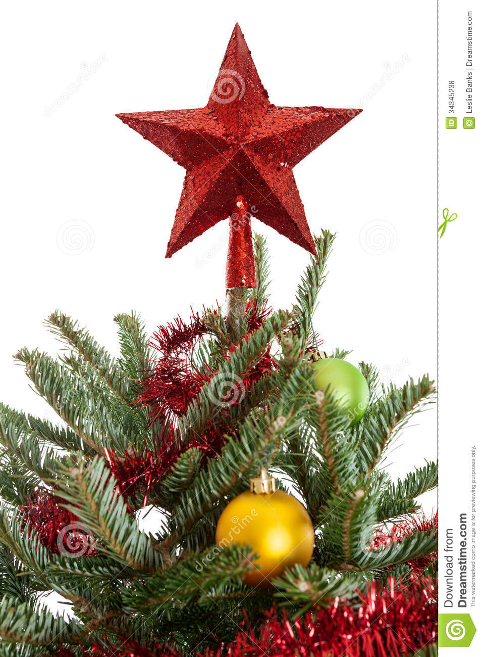 Of a red star on top of a decorated christmas tree isolated on white