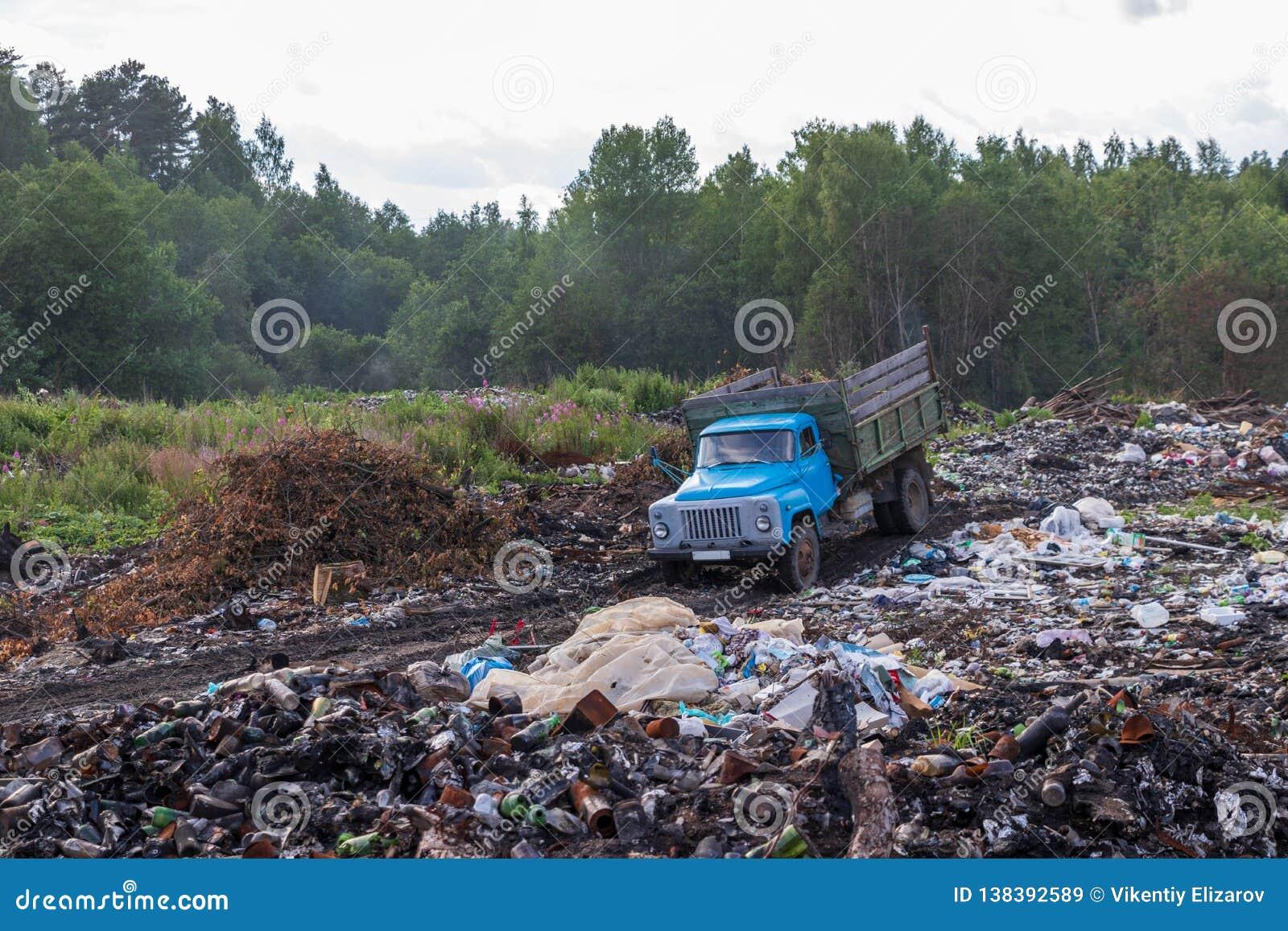 Stara śmieciarska ciężarówka jedzie na bezprawnym śmieciarskim usypie w drewnach