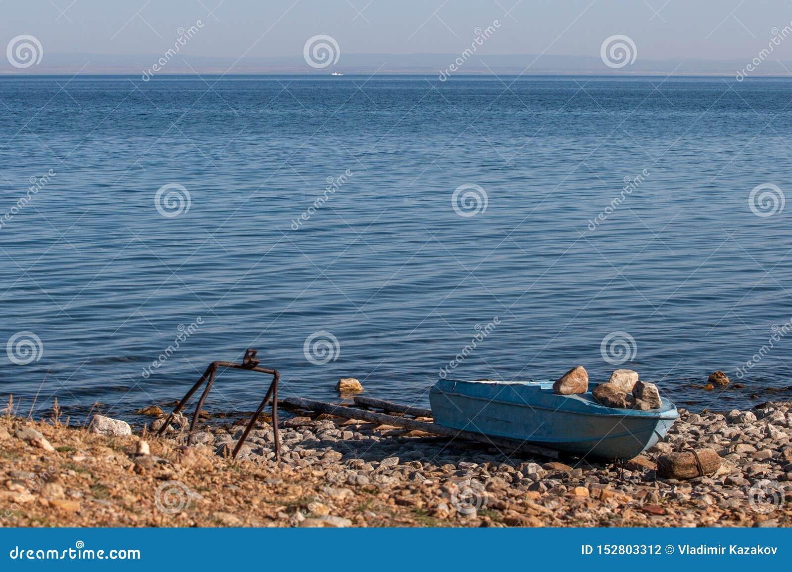 Stara żelazna łódź rybacka na brzeg błękitny Jeziorny Baikal Naciskający puszek wielkimi kamieniami