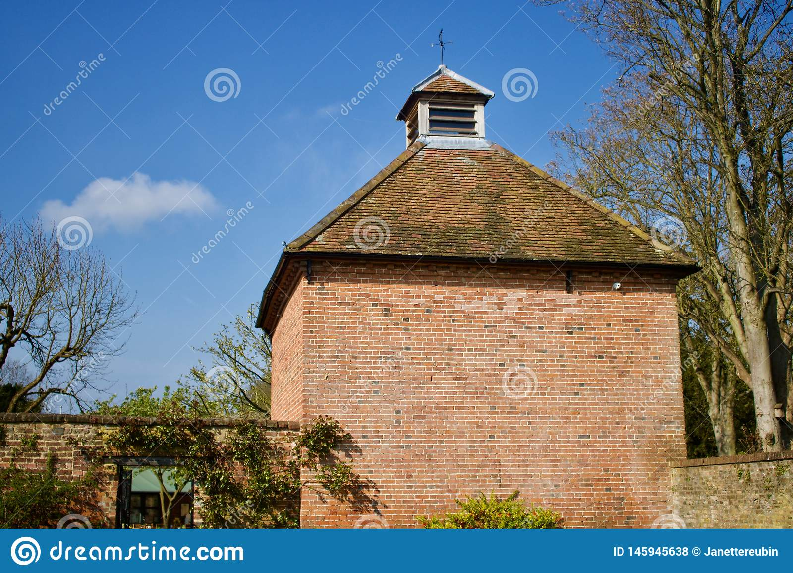 Stara cegła budował gołąbki cote z terakota taflującym dachem przeciw niebieskiemu niebu - wizerunek