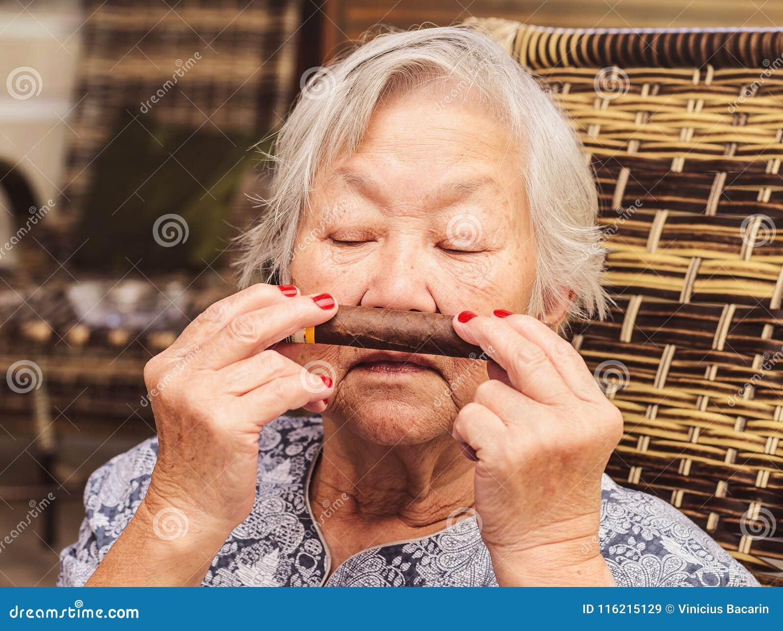 Stara dama docenia kubańskiego cygaro Dama wącha cygaro