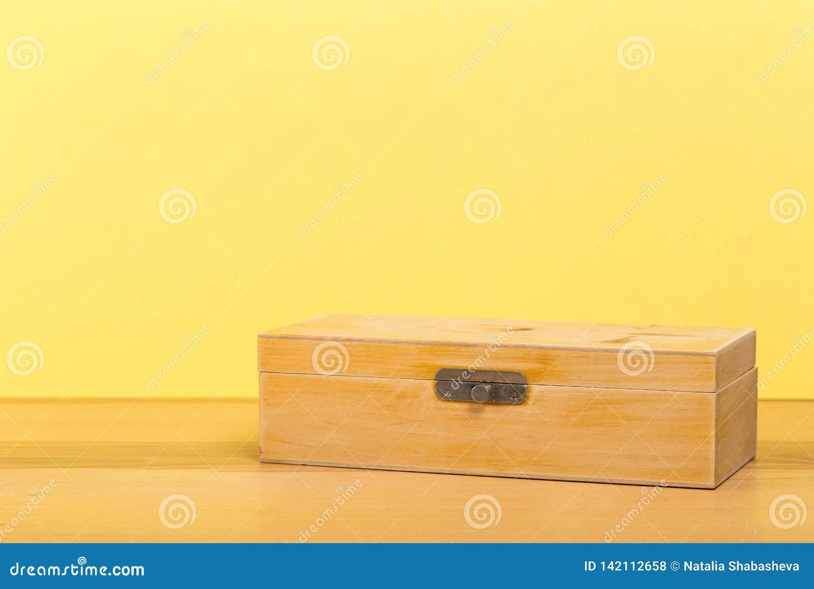 Stara handmade szkatuła na drewnianym stole z kolor ściany tłem