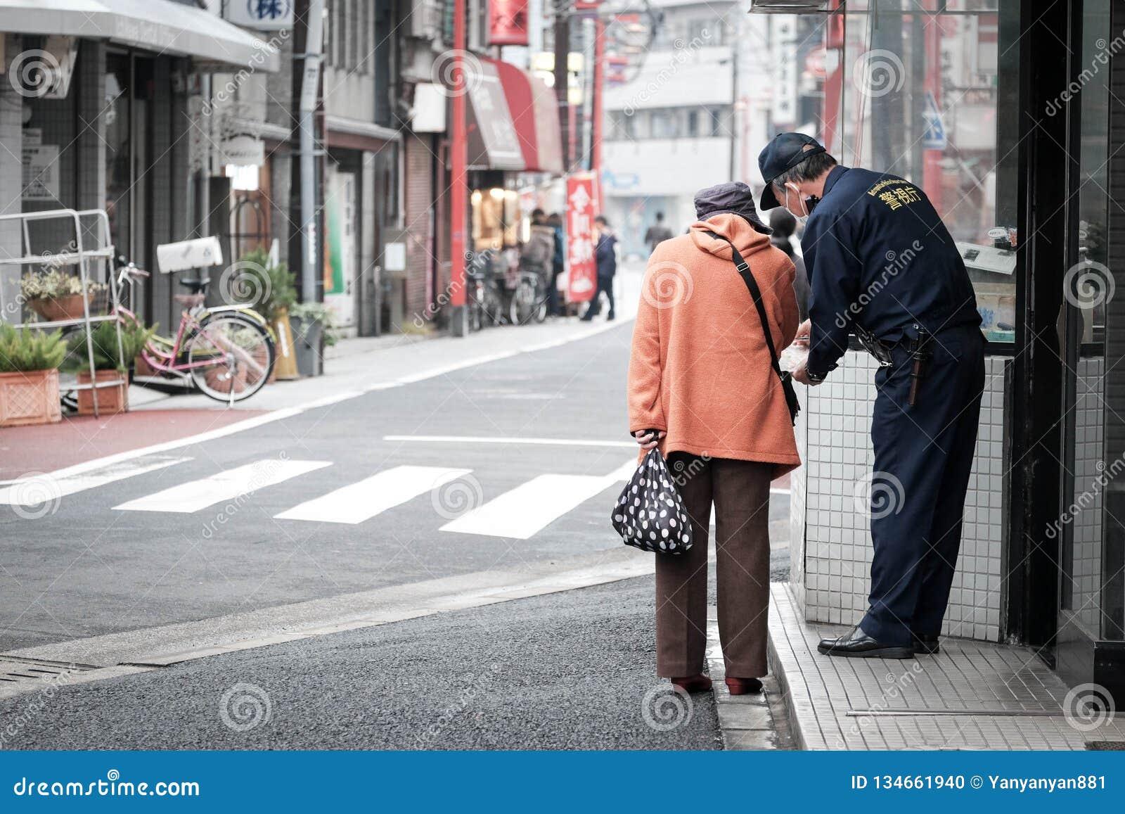Stara kobieta pyta dla kierunku od policji na ulicie Japan