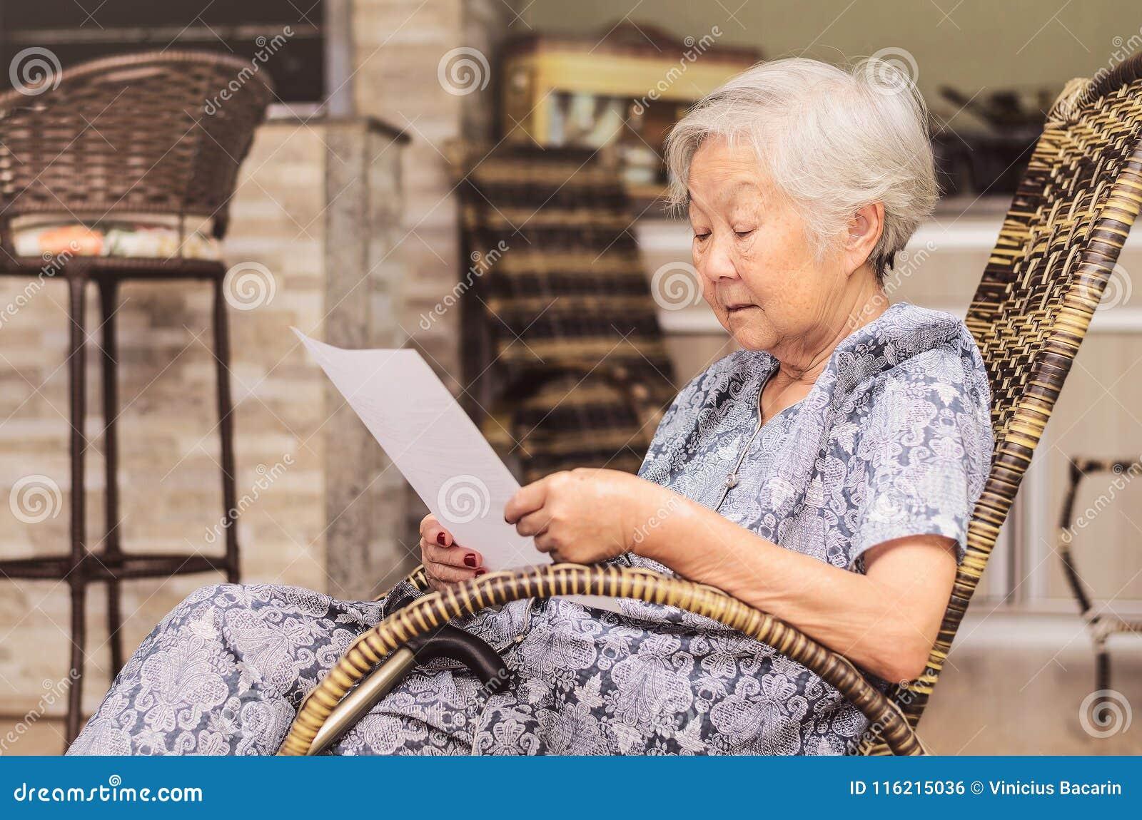 Stara kobieta sadzał czytanie ostrożnie dokument lub terminy insu