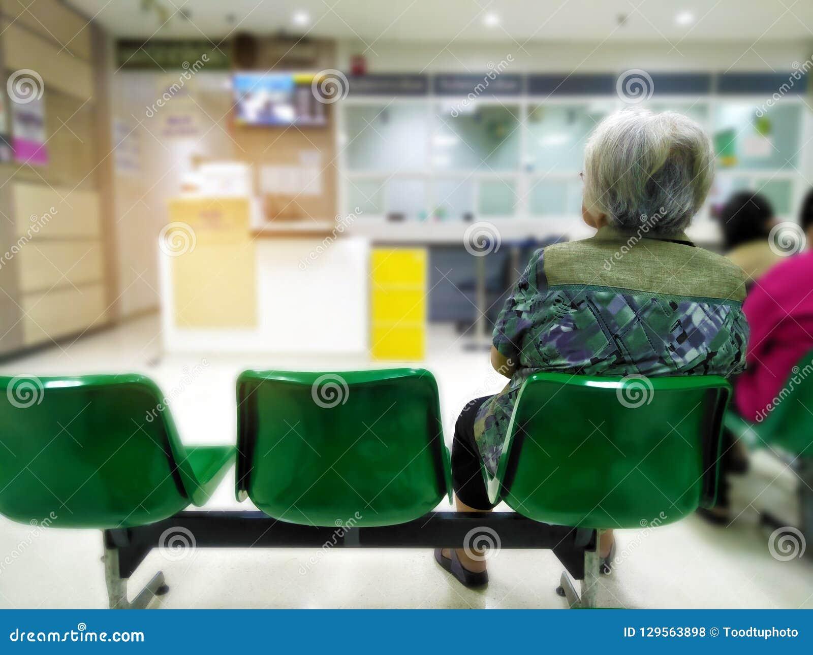 Stara kobieta siedzi na zielonym krzesła czekaniu medycznym szpital i usluga zdrowotna