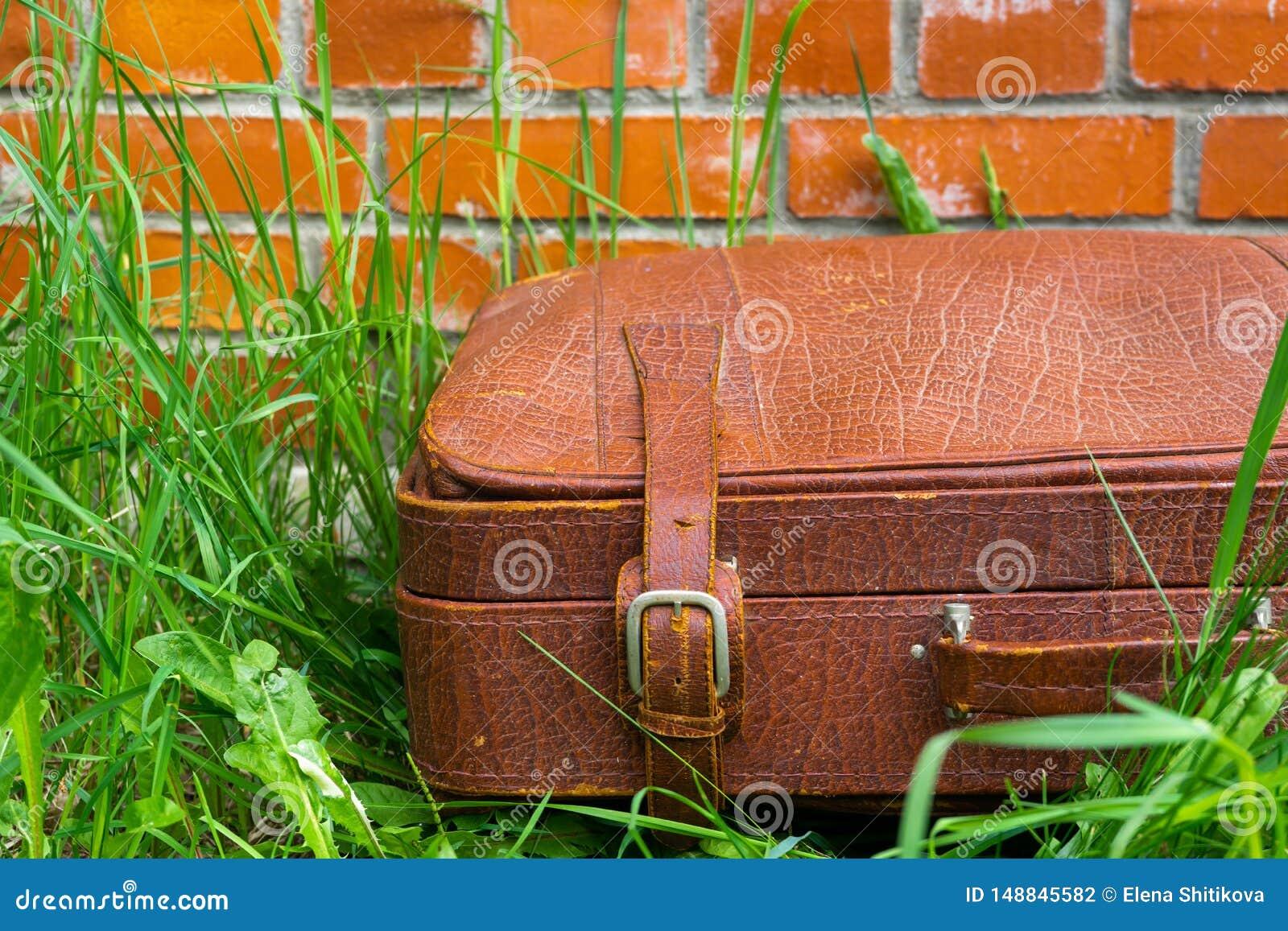 Stara podława walizka przeciw tłu ściana z cegieł