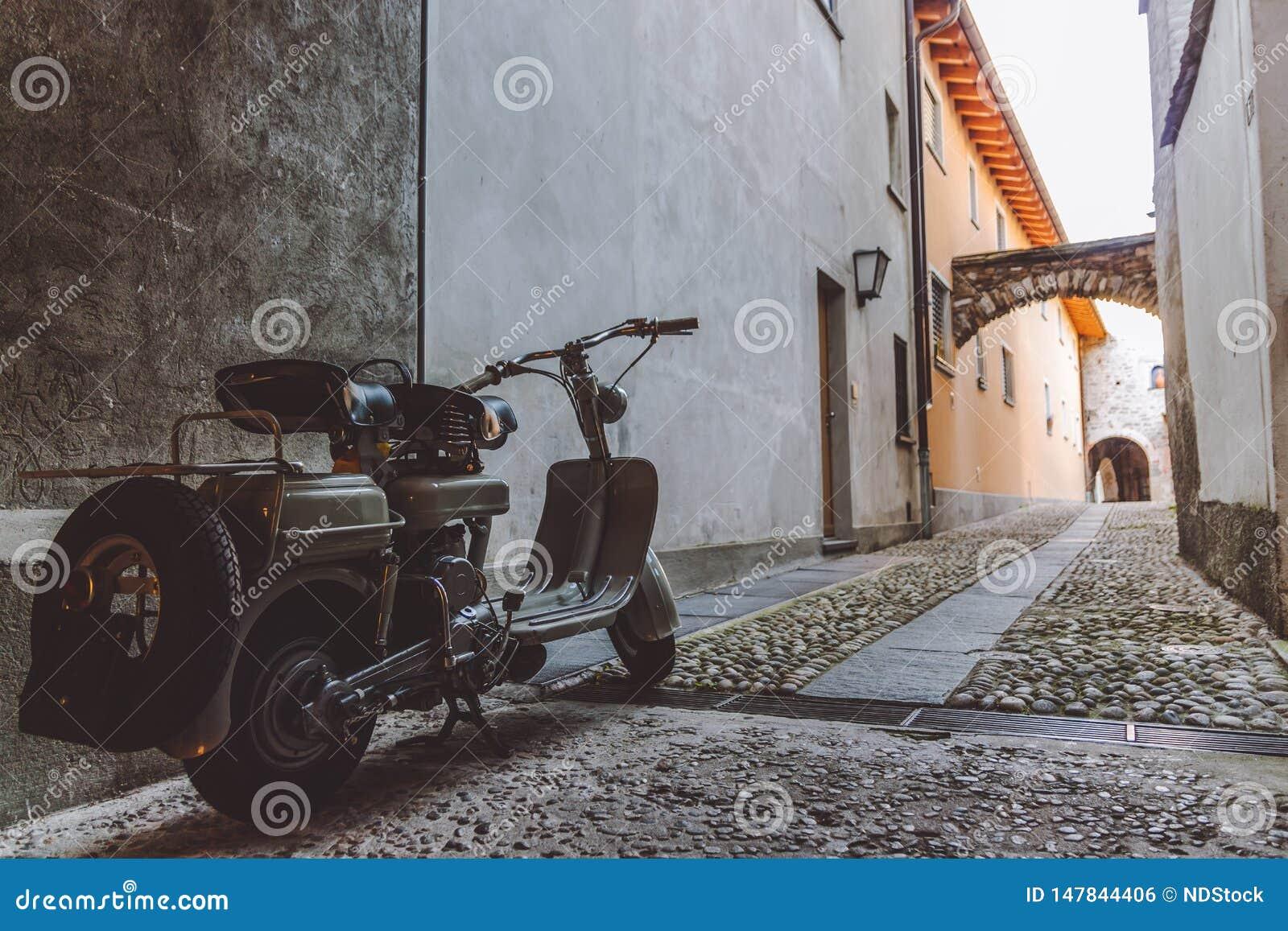 Stara popielata hulajnoga parkująca w wąskiej alei w Ascona
