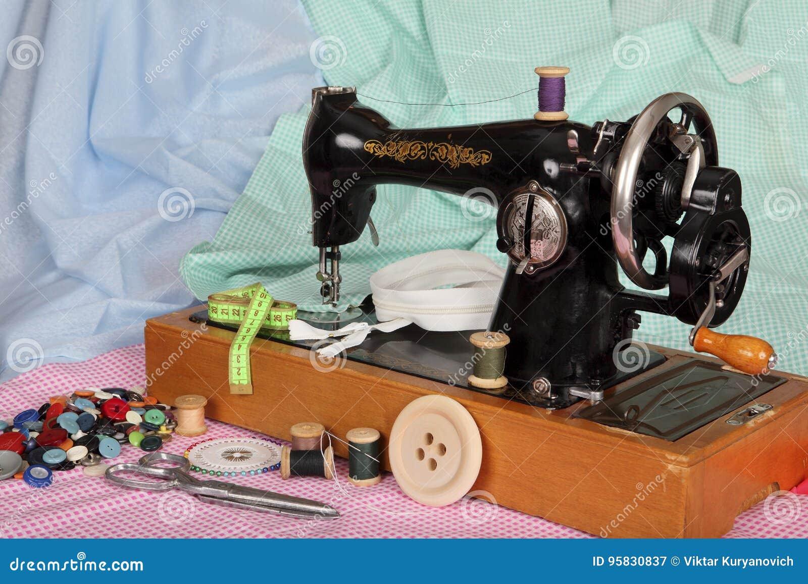 Stara, ręka szwalna maszyna z igłą, retro zwitki z barwionymi niciami, jaskrawi guziki i kawałki barwiona bawełniana tkanina,