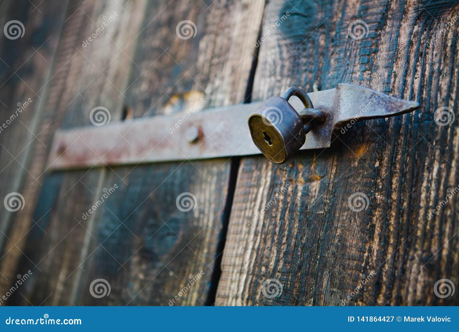 Stara rocznik kłódka na drewnianych drzwiach Płytka ostrość - Ośniedziała