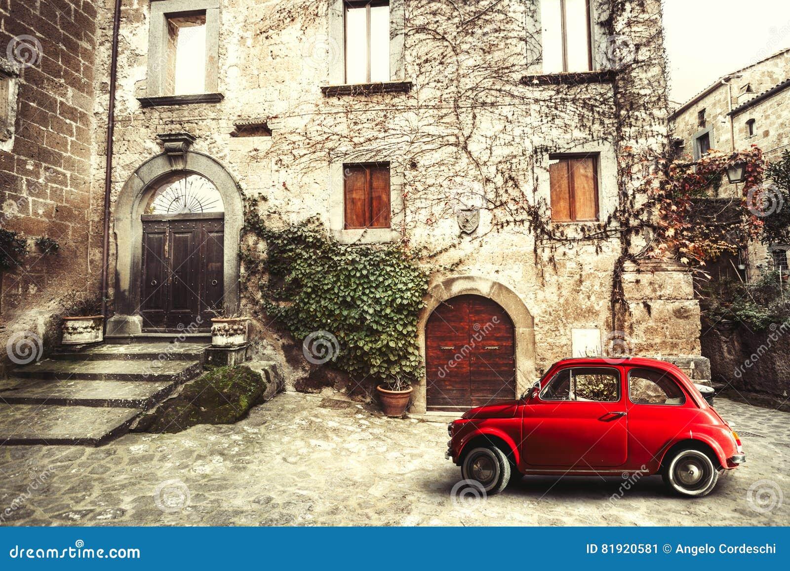 Stara rocznika włocha scena Mały antykwarski czerwony samochód Fiat 500