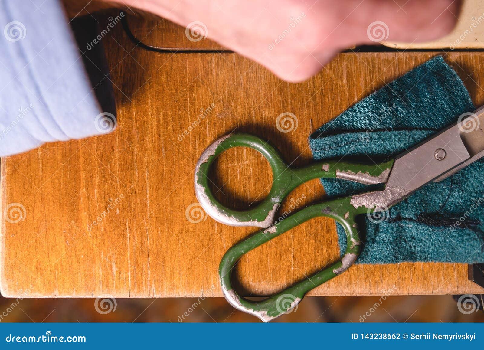 Stara szwalna maszyna z nożycami, na starym grungy praca stole Krawiecki ` s pracy stół tkanina lub świetny sukienny robić przemy
