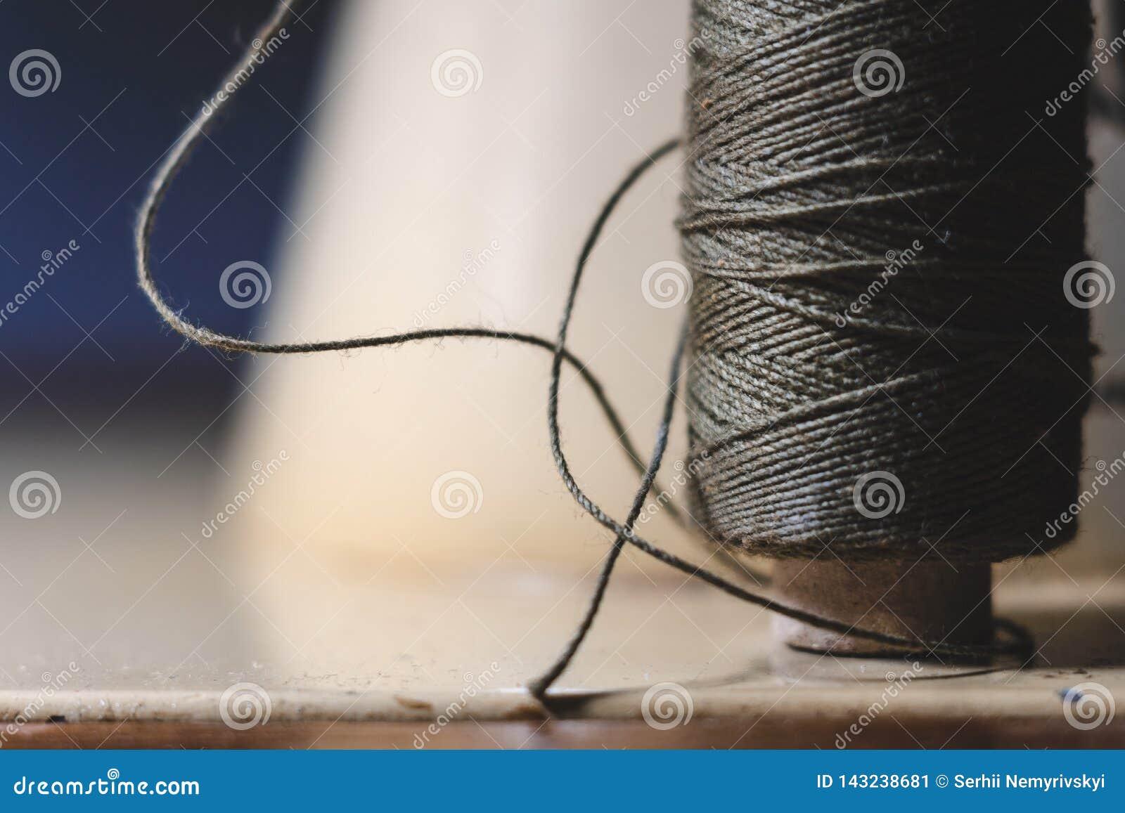 Stara szwalnej maszyny ig?a z czarn? nici? na starym grungy praca stole, Krawiecki ` s pracy st?? tkanina lub ?wietny sukienny ro