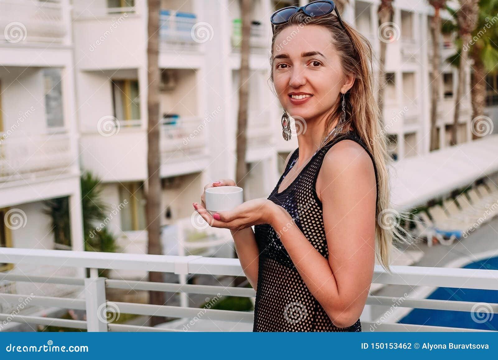 Stara uśmiechnięta kobieta z filiżanka kawy na balkonie hotel na wakacje