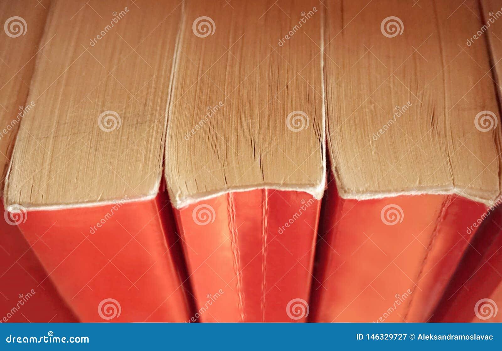 Stare książki z czerwoną książkową pokrywą brogującą pionowo na półkach na widok