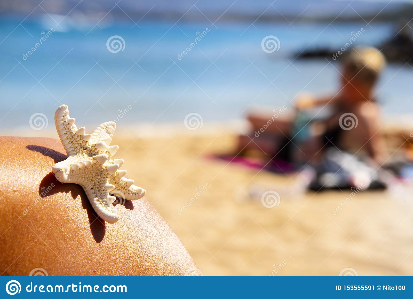 Starfish and person relaxing on the beach