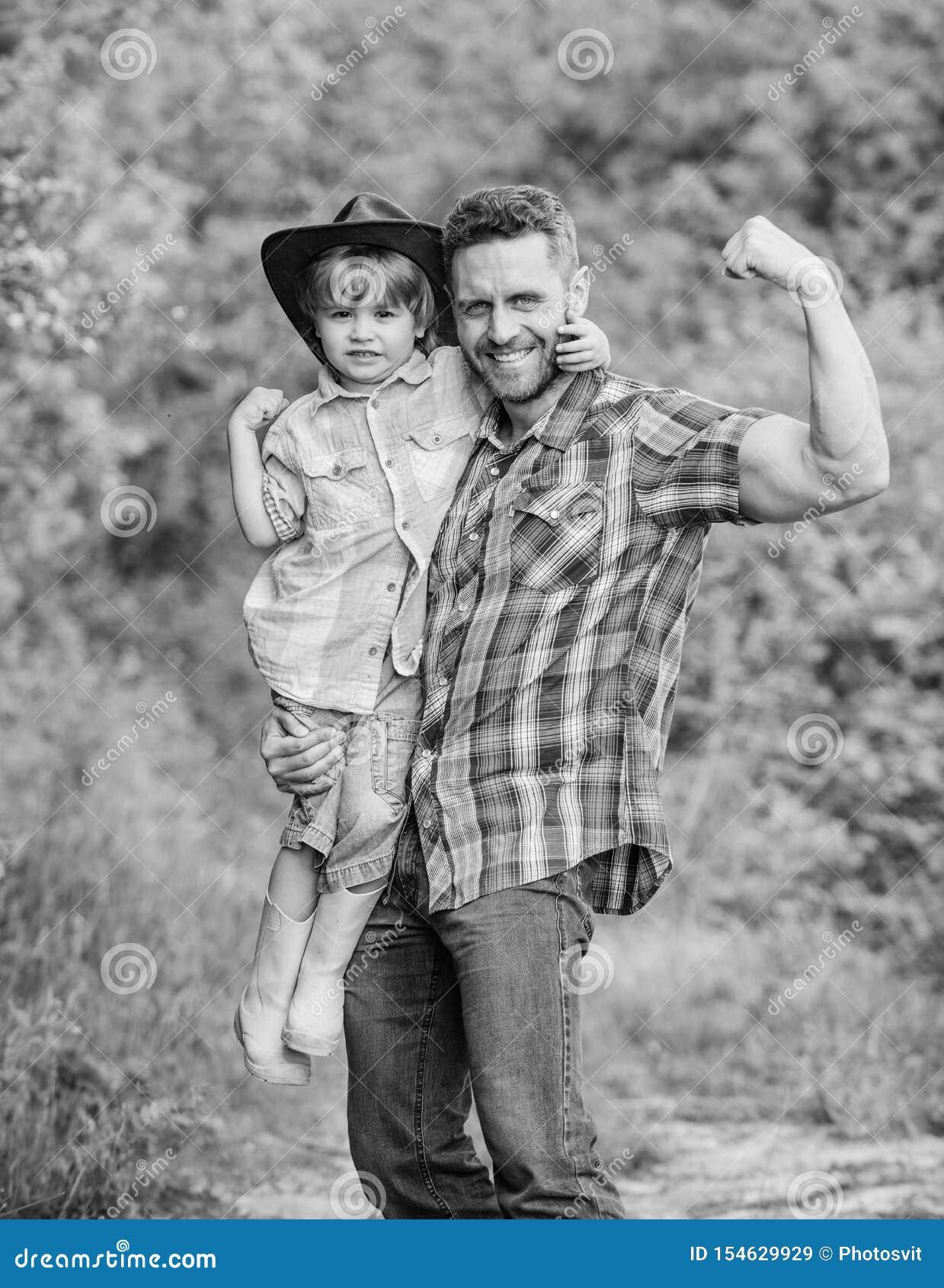Stark fader och son i cowboyhatt p? ranch unge i gummist?veler E Familjdag