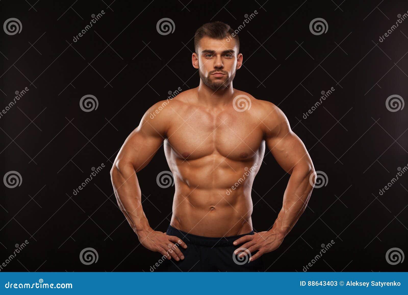 Stark idrotts- man - konditionmodell som visar hans torso med sex packeabs Isolerat på svart bakgrund med Copyspace