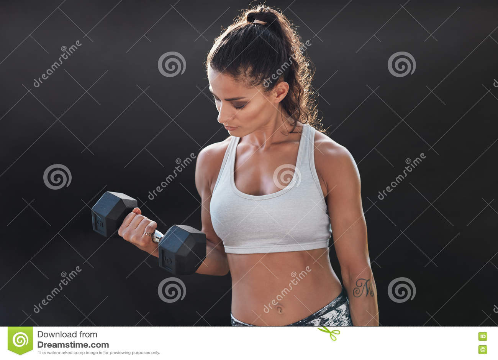 Stark och muskulös kvinnlig som övar med hanteln