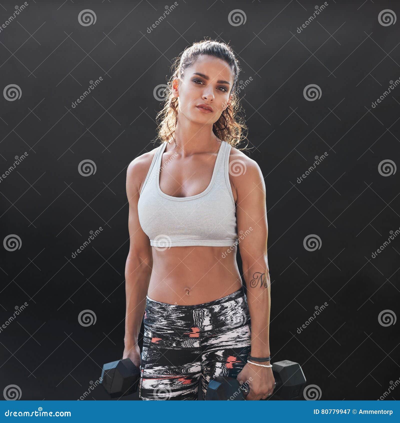 Stark och muskulös kvinnlig som gör bodybuildingutbildning