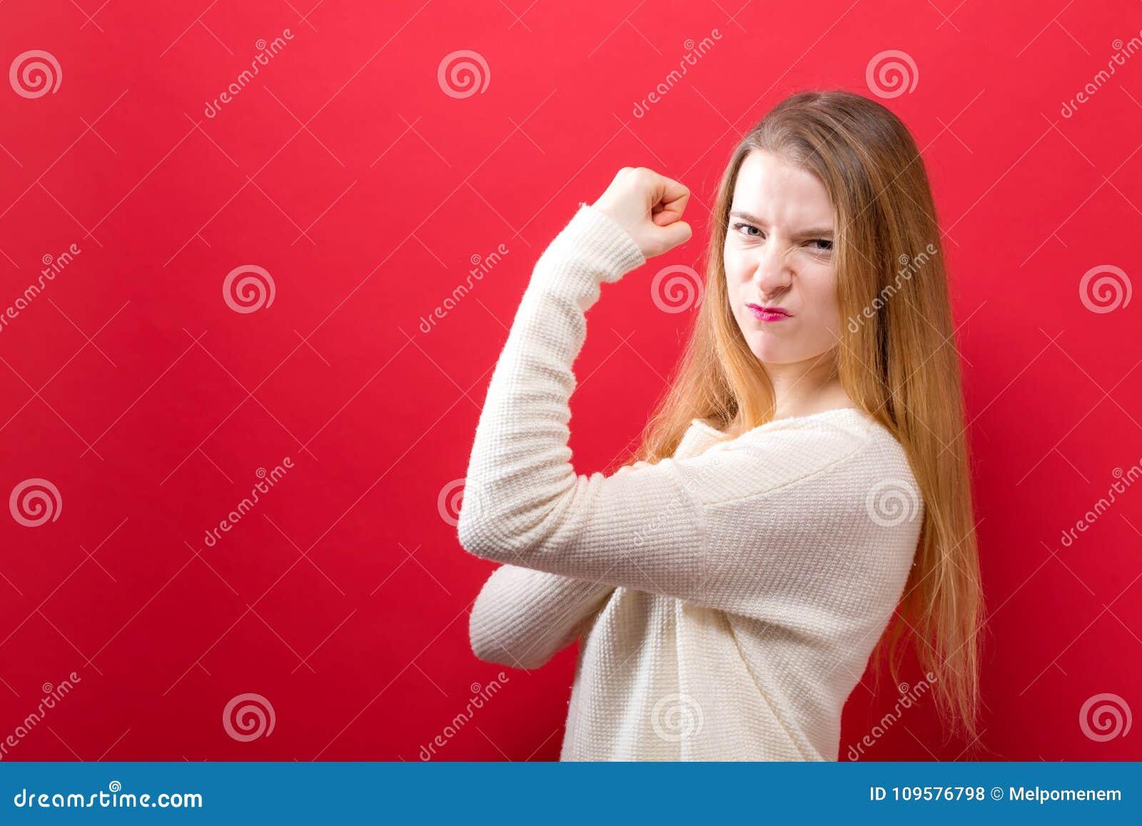 Starke junge Frau in einer Erfolgshaltung
