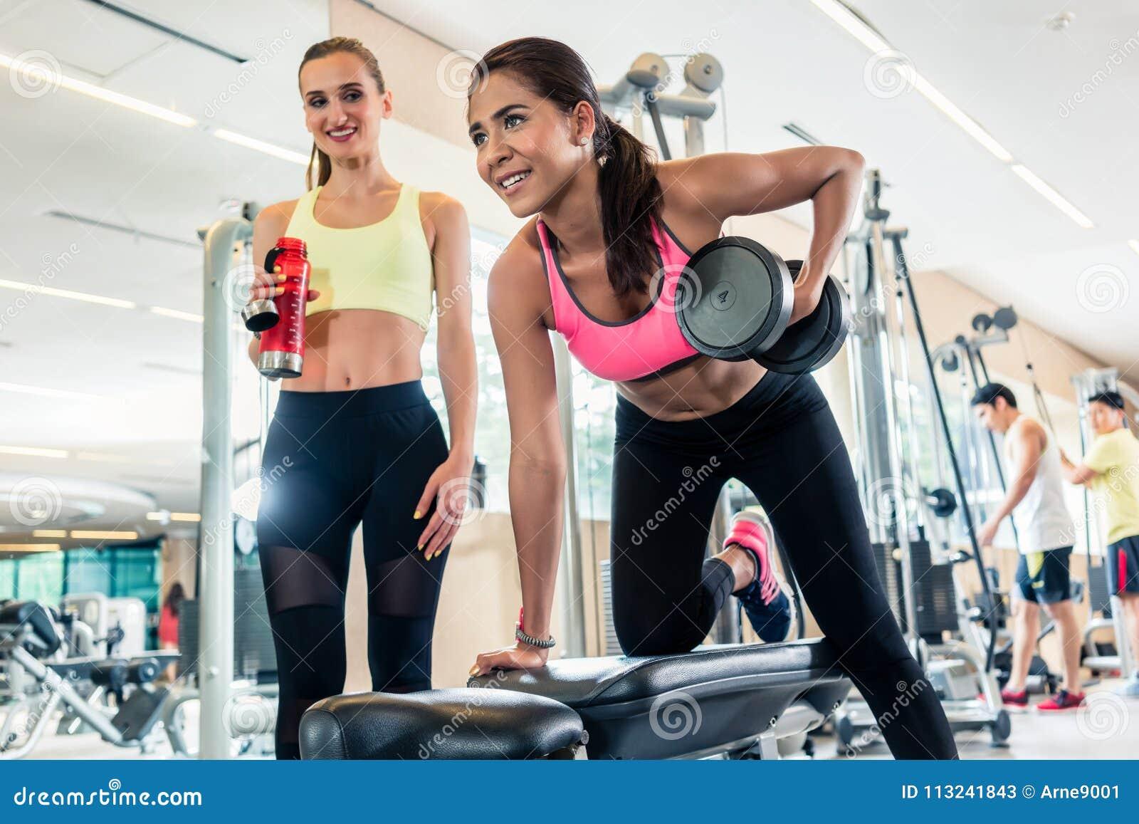 Starke junge lächelnde Frau beim Rudern mit einem Arm