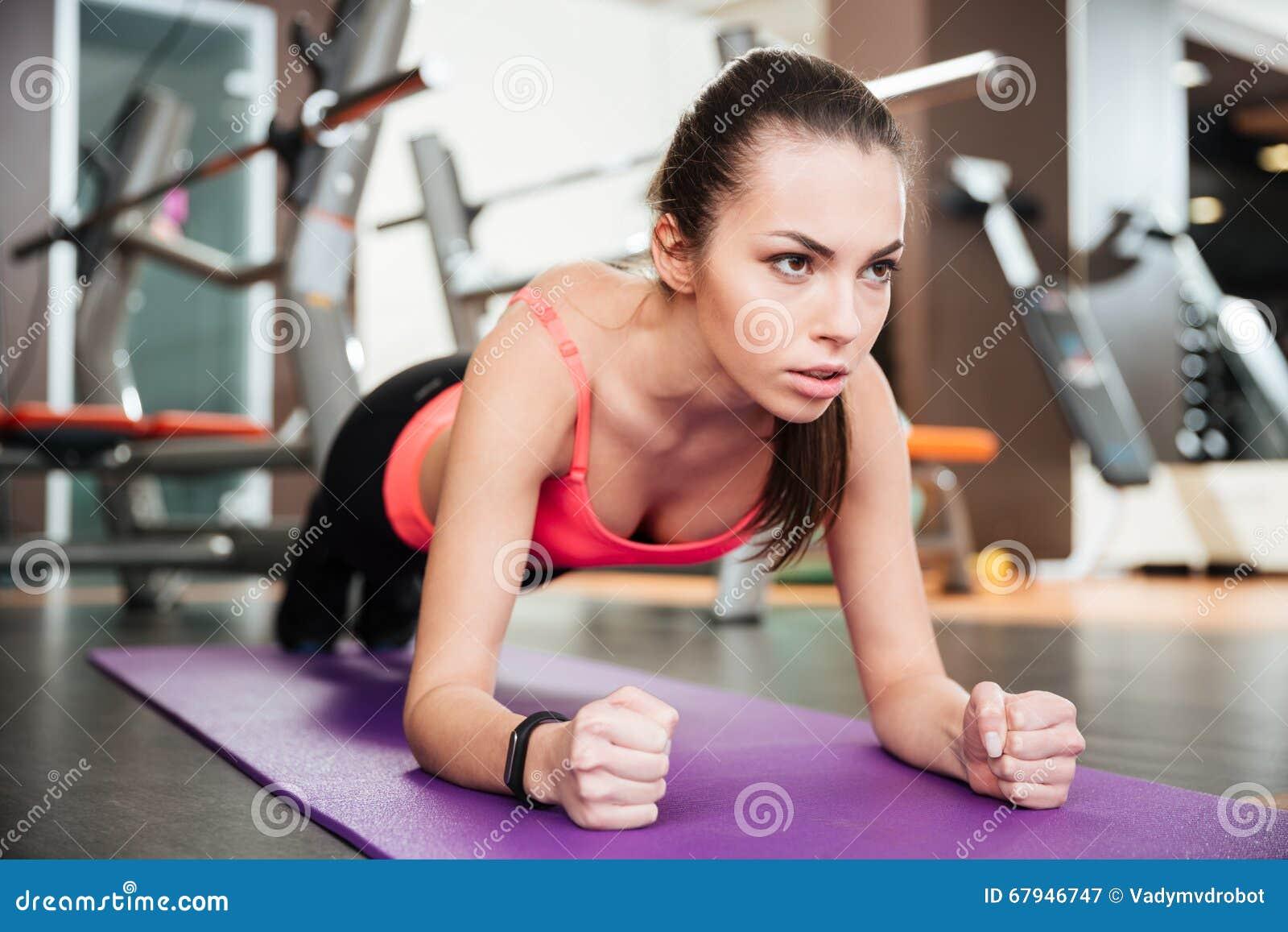 Starke schöne junge Sportlerin, die Plankenübung tut