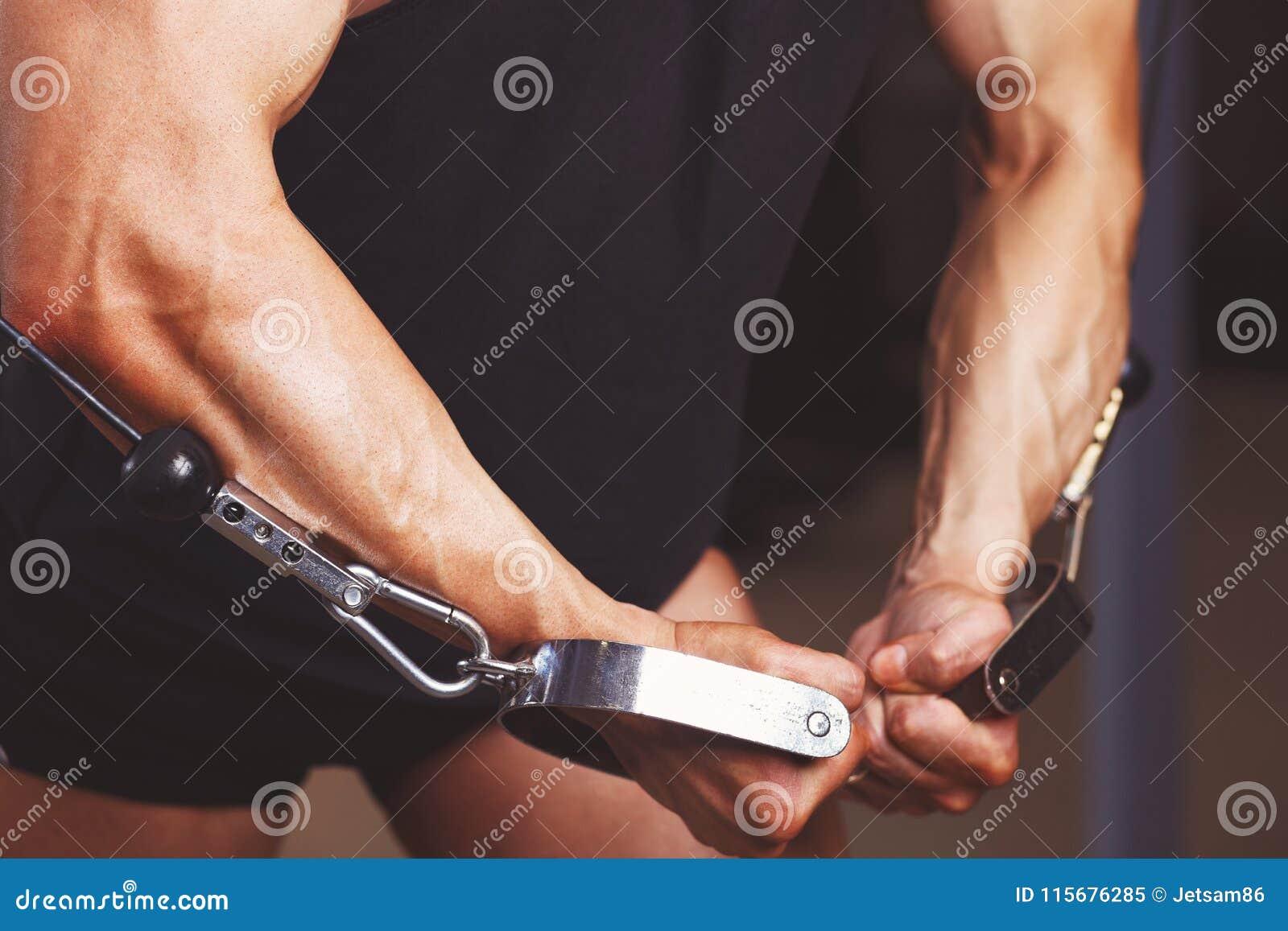 Starke zerrissene angespannte Mannhände, die oben im Turnhallenabschluß ausarbeiten