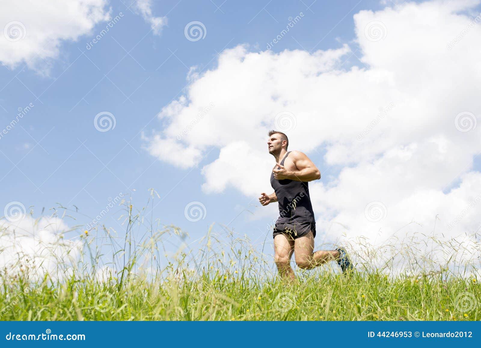 Starker athletischer Mann, der auf dem Feld läuft