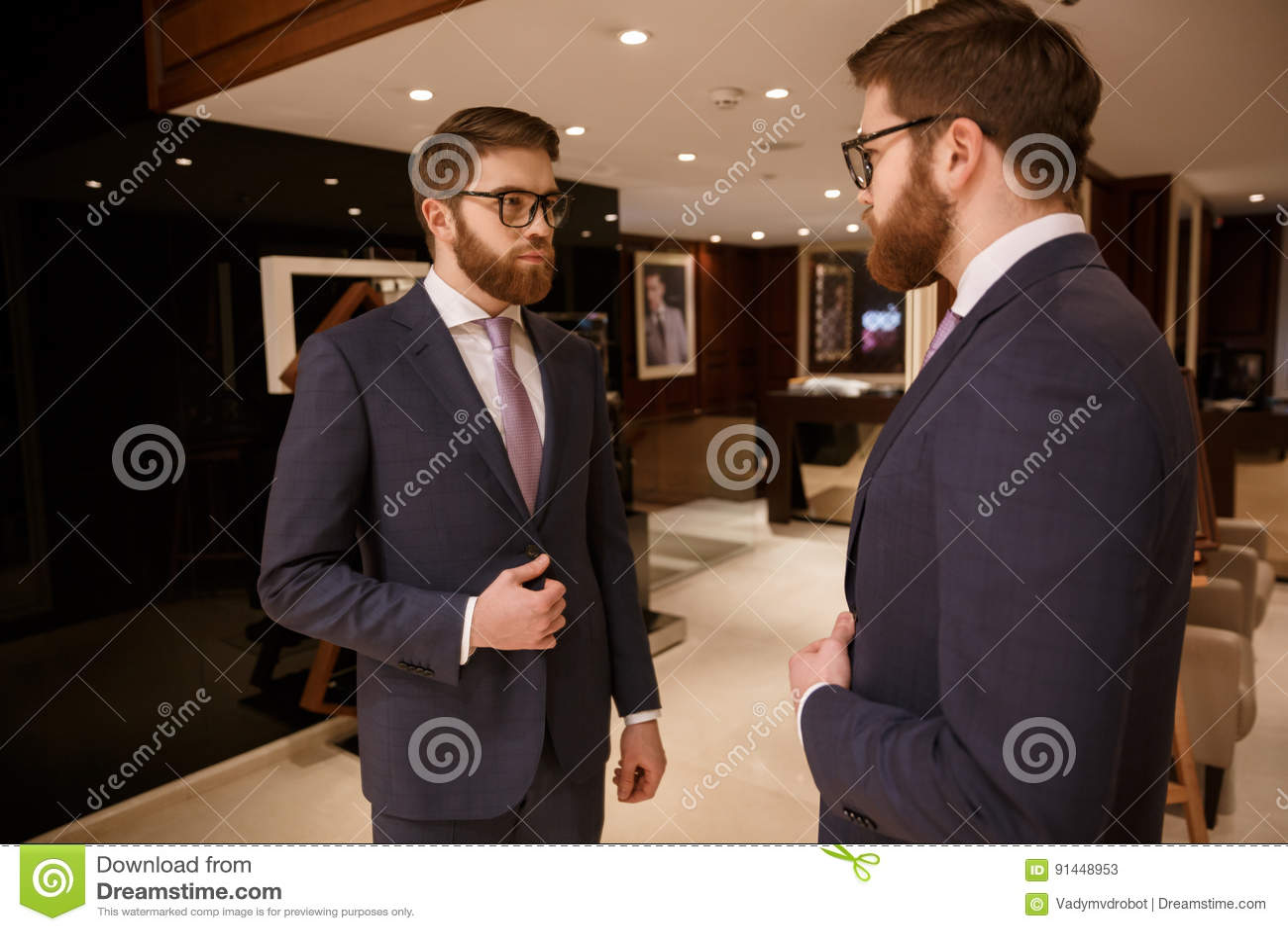 Starker junger bärtiger Geschäftsmann, der zuhause steht