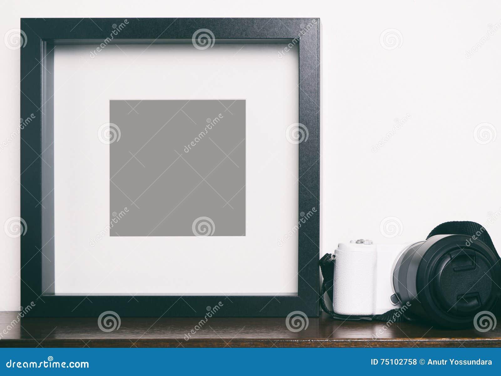 Starker leerer schwarzer Fotorahmen auf Regal mit Kamera