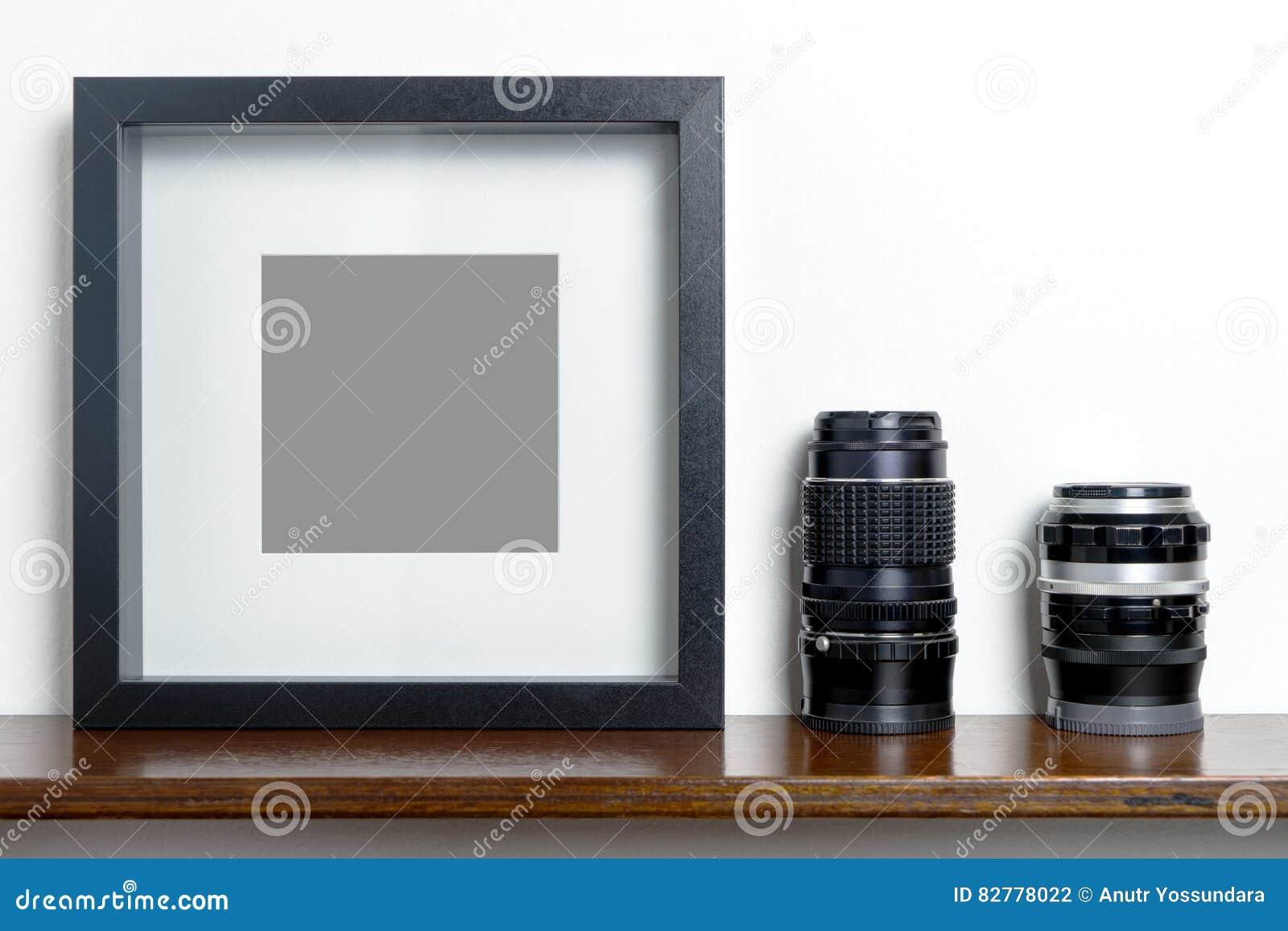 Starker leerer schwarzer Fotorahmen auf RegalKameraobjektiv