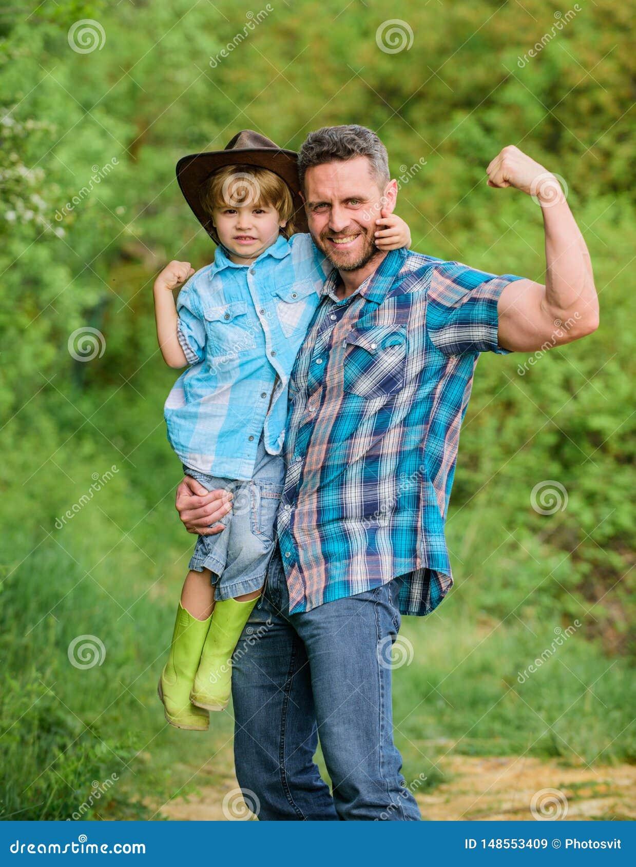 Starker Vater und Sohn im Cowboyhut auf Ranch Kind in den Gummistiefeln Gl?cklicher Mannvati im Waldmenschen und -natur Familient