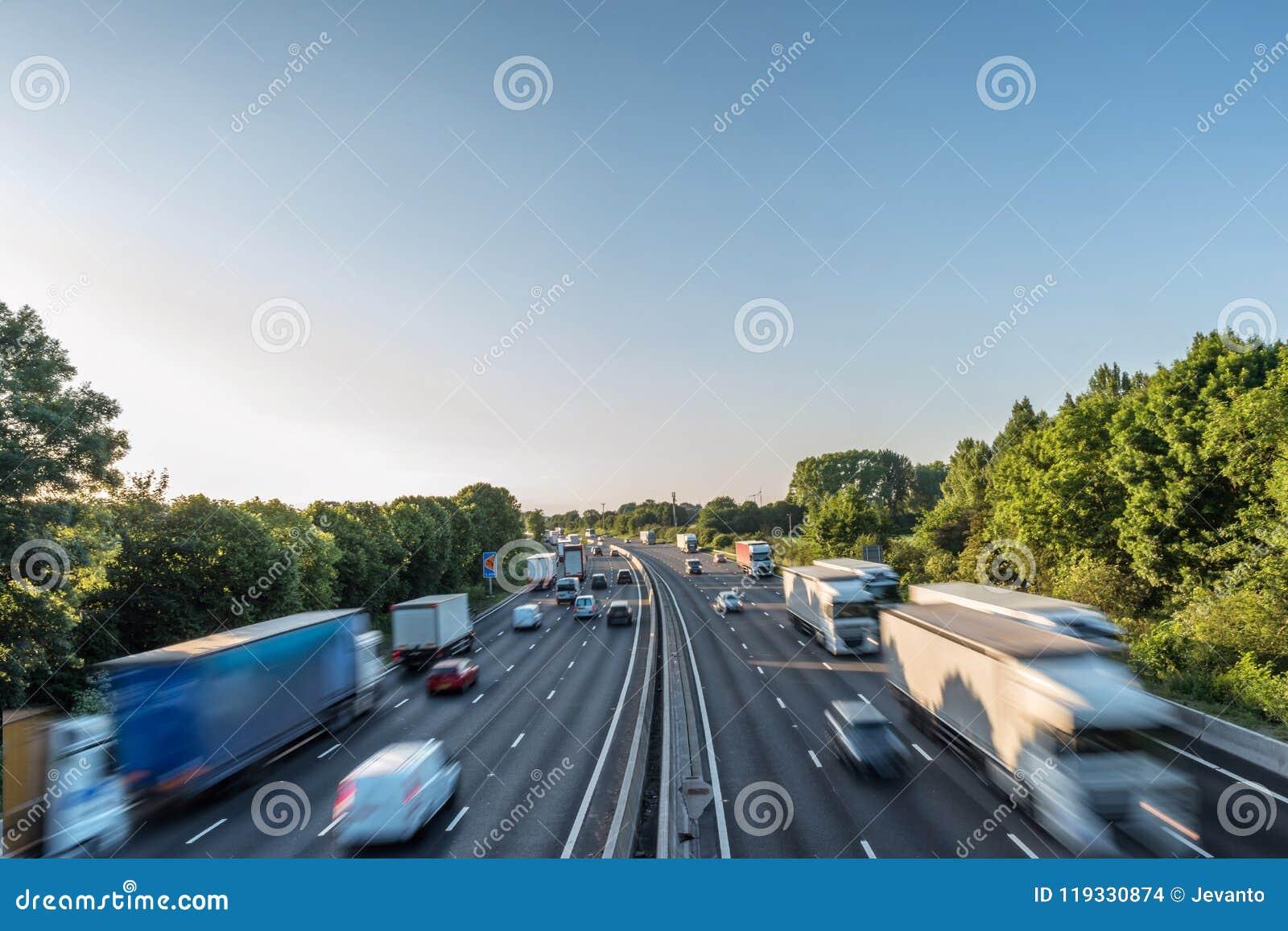 Starker Verkehr der Sonnenuntergangansicht, der mit Geschwindigkeit auf BRITISCHER Autobahn in England sich bewegt
