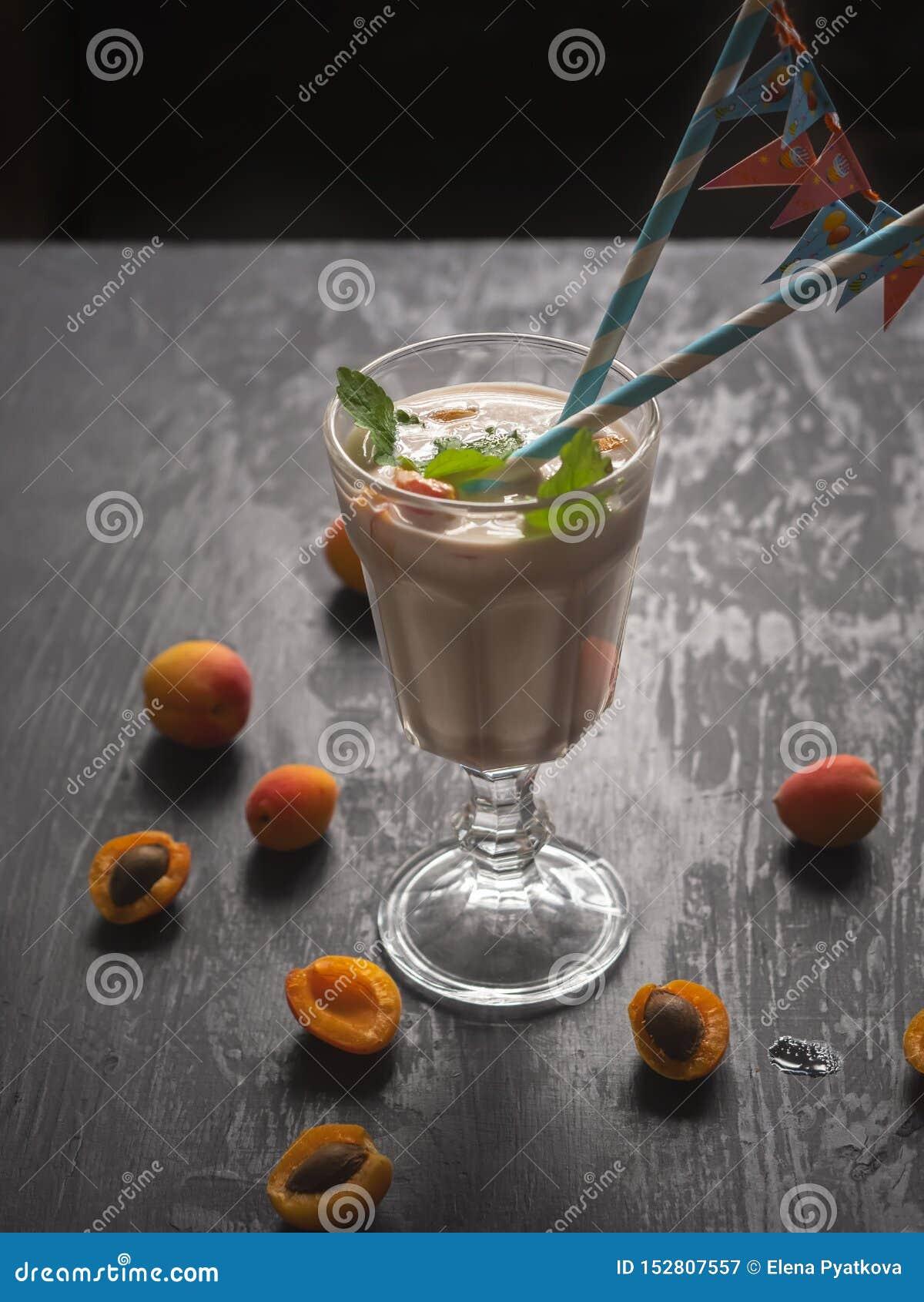 Starkes Milchshake mit Frucht, Aprikosen und Banane in einem großen Glasbecher Papierrohre mit Flaggen während eines hellen Festt