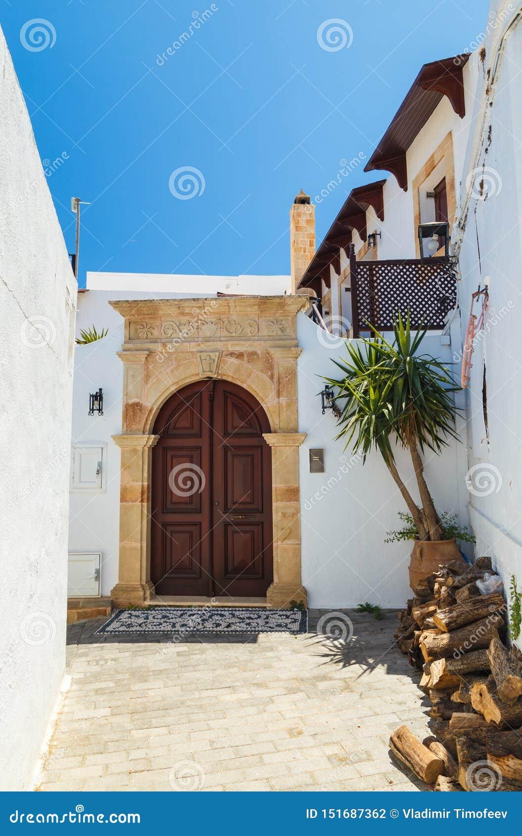 Starożytny Grek architektura z tradycyjnymi drzwiami i dekoracyjnym brukiem w Lindos miasteczku, Rhodes wyspa, Grecja, Europa