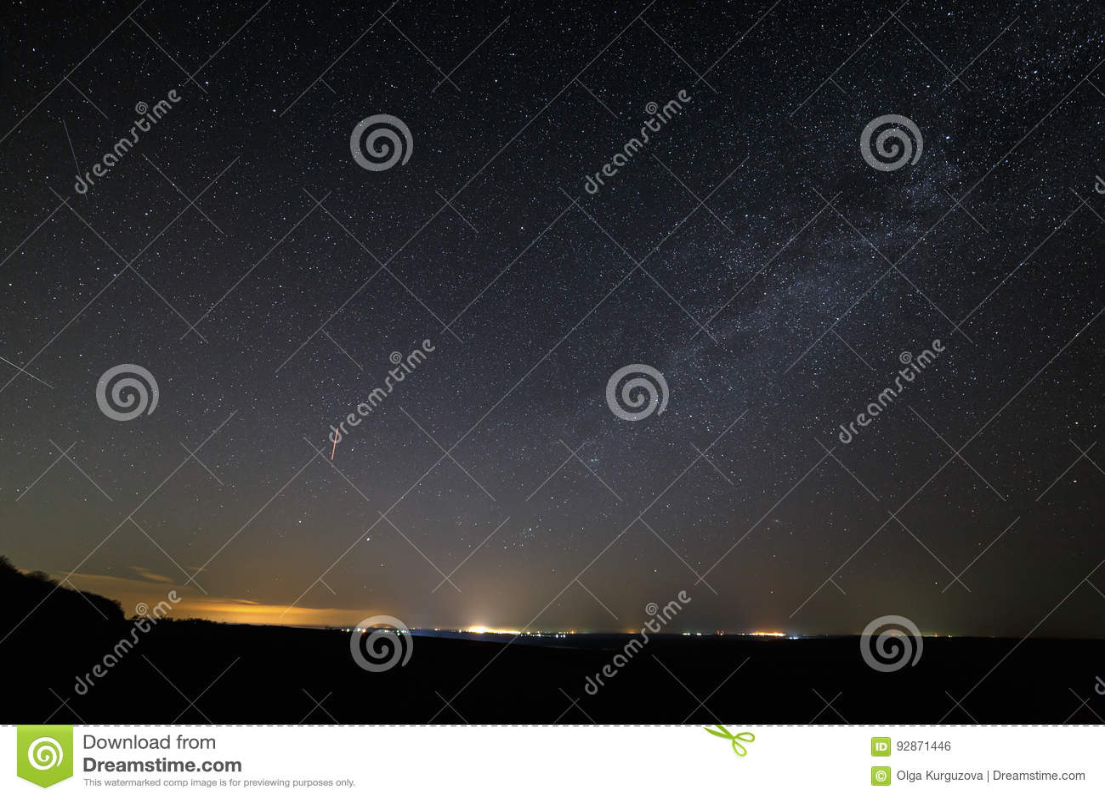 Stars in dark night sky with city lights on the horizon.