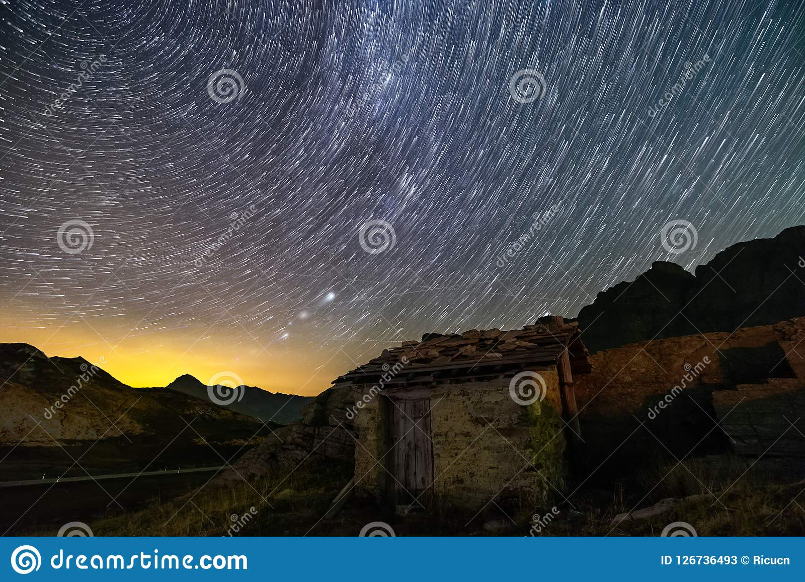 Stars trails and isolated house in switzerland alps