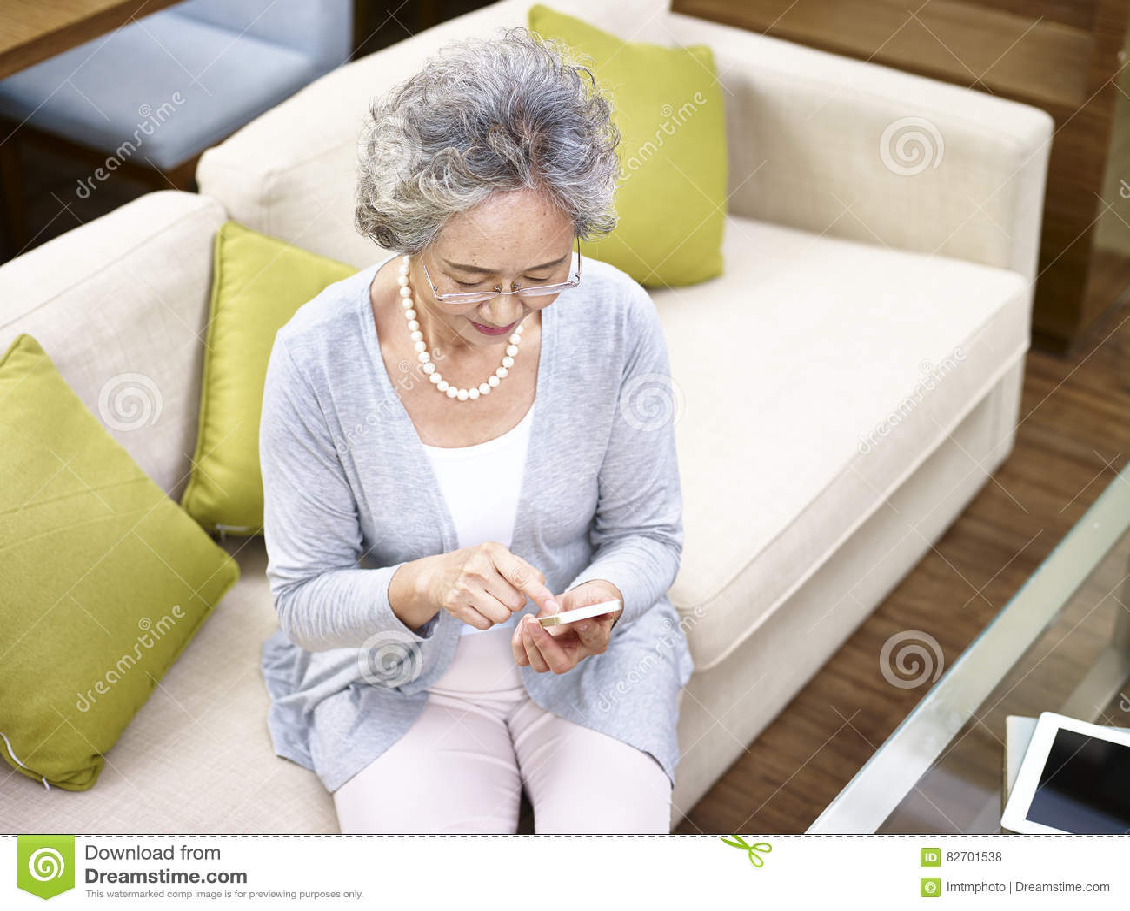 Starsza azjatykcia kobieta używa telefon komórkowego