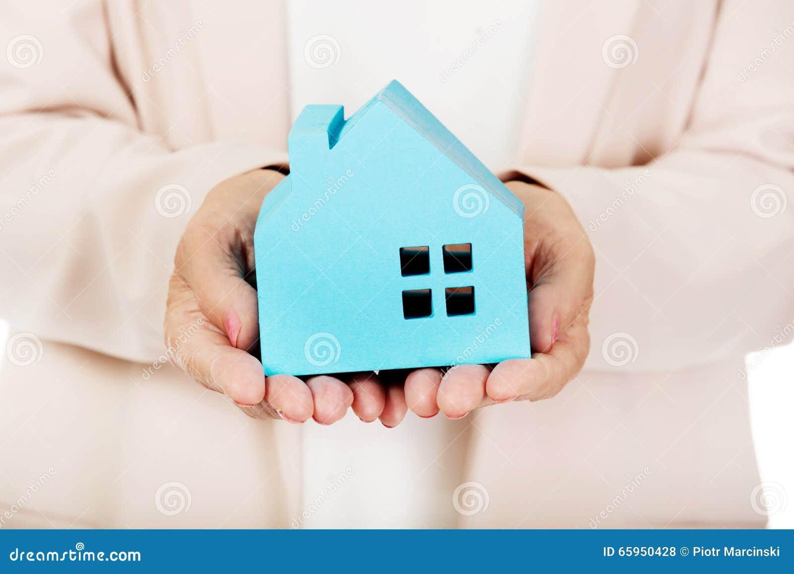 Starsza biznesowa kobieta trzyma błękitnego papieru dom