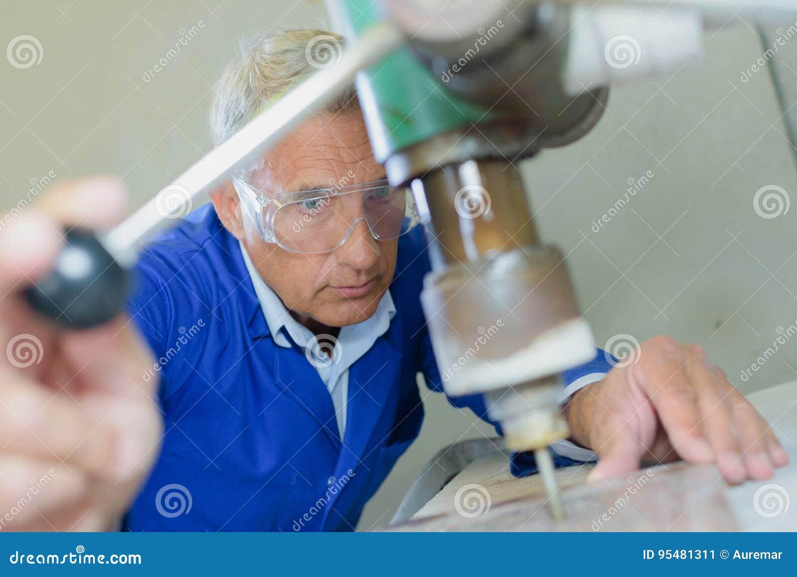 Starsza cieśli musztrowania dziura w desce w warsztacie