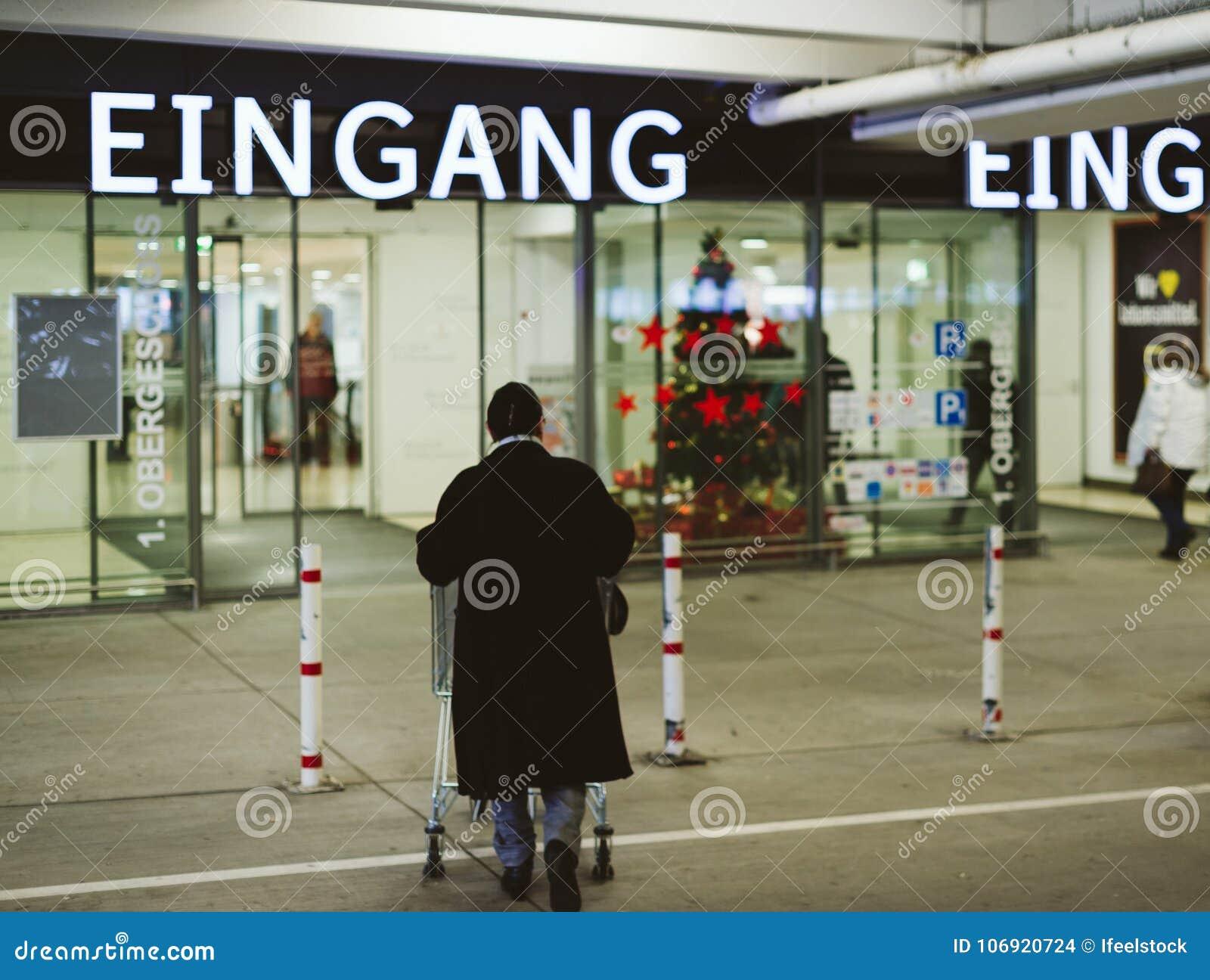 Starsza kobiet pchnięć supermarketa fura wejście edeka sklep