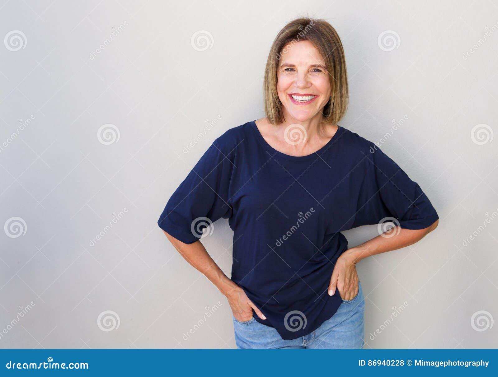 Starsza kobieta śmia się przeciw szarości ścianie